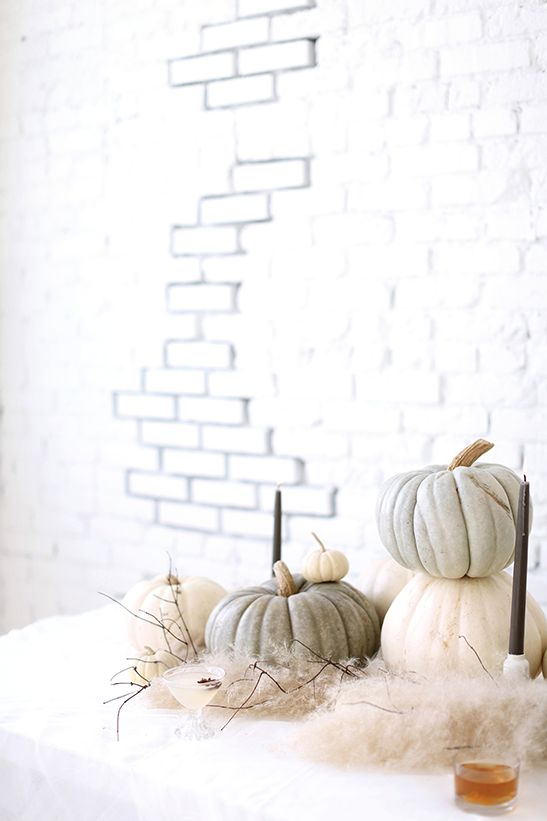 neutral pumpkins of green shades, with black candles and in faux fur look realy chic