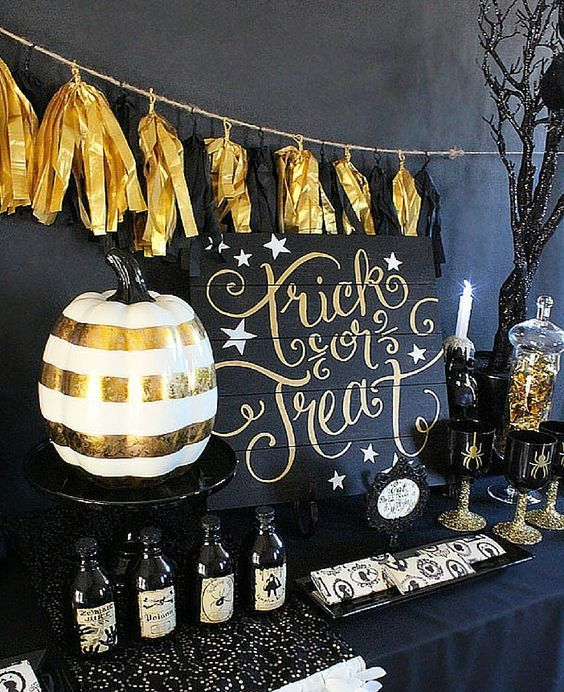 a Halloween dessert table with a black and gold garland, a gold and white pumpkin and some scary desserts and drinks
