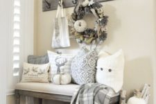 11 a bench with pillows, a crate with white pumpkins, a wreath with pumpkins and pinecones