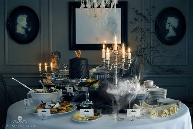 a glam and decadent Halloween dessert table with vintage candle holders and a black cake