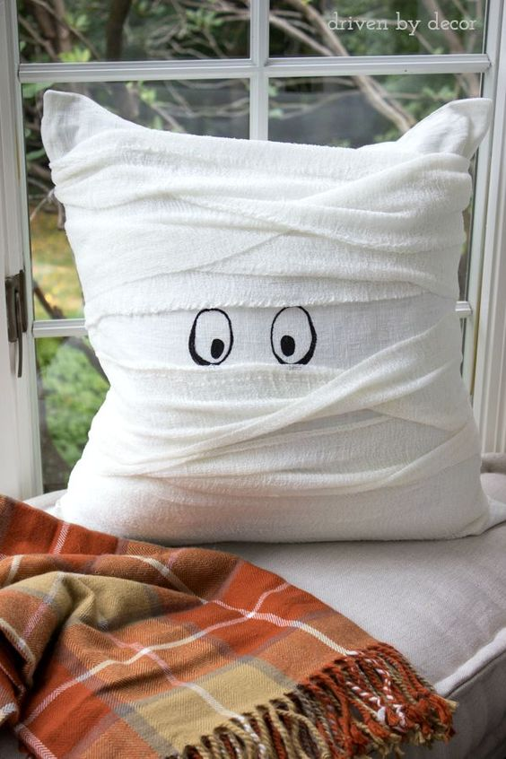 a pillow wrapped with white cheesecloth and with painted eyes as a cute mummy pillow