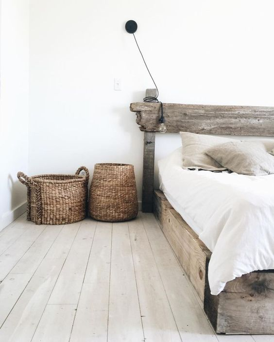 a reclaimed wood bed and wicker baskets give this neutral space a cool rustic feel