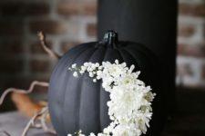 11 elegant matte black pumpkin with white flowers is a chic decoration