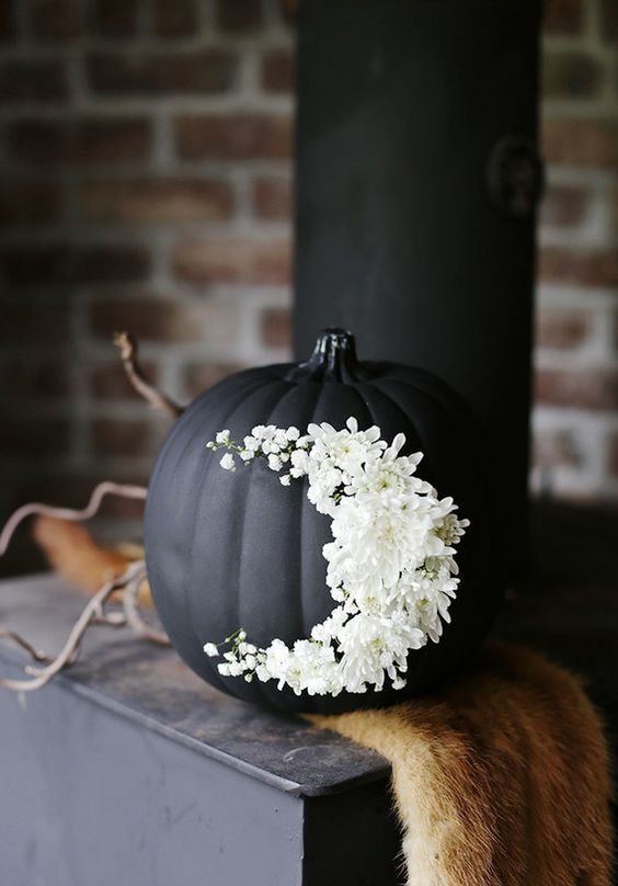 elegant matte black pumpkin with white flowers is a chic decoration