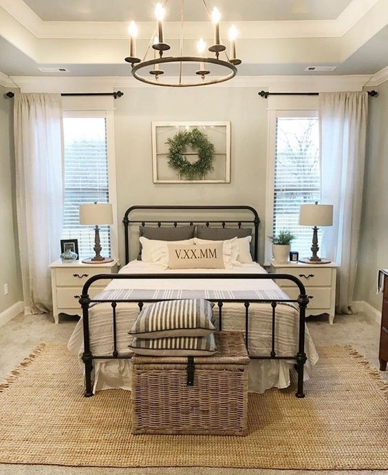 a cozy farmhouse bedroom with jute rugs, a wicker chest, a metal bed and vintage nightstands