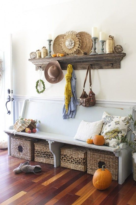 a dusty blue bench, wicker crates under it, some pumpkins on display