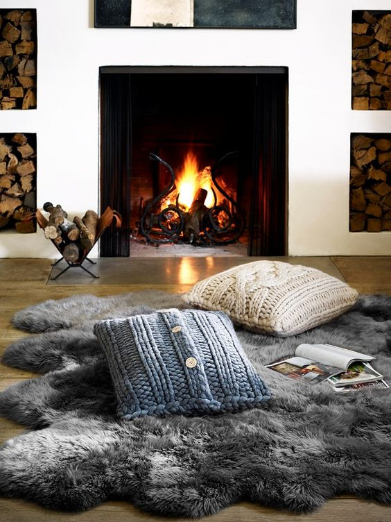 a fireplace nook with a faux fur rug and knit pillows for cuddling