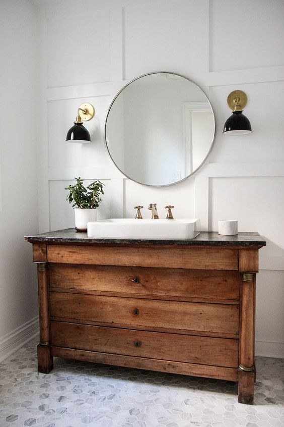 a rustic wood vanity with a stone counter adds a vintage and cozy feel