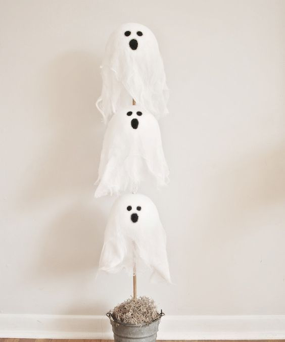 a simple ghost display in a bucket, the ghosts ar emad eof cheesecloth