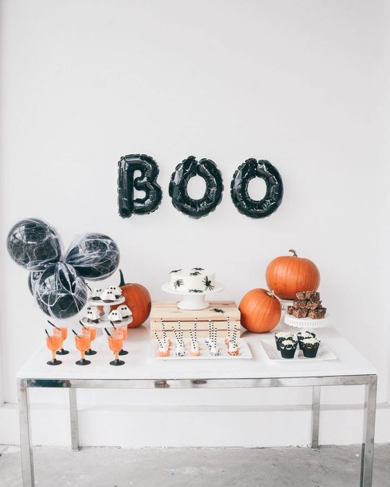 a simple modern dessert table with black letter balloons and orange pumpkins