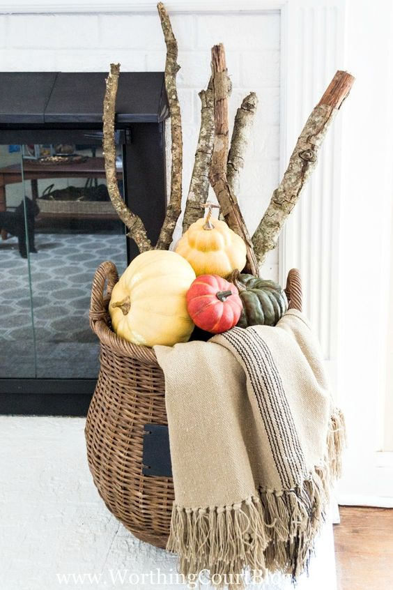 a tall basket with colorful pumpkins, branches and a blanket