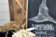 13 a chalkboard sign with a witch-inspired artwork