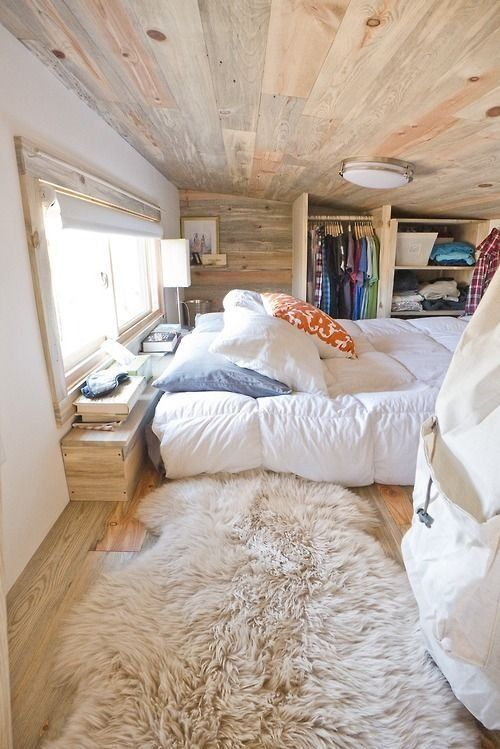 a lush faux fur rug adds texture and warmth to this wood clad bedroom