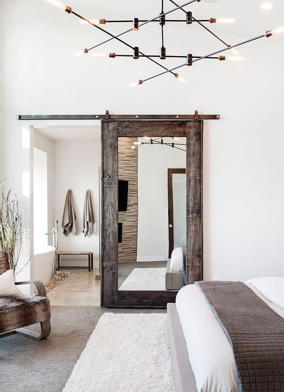 a reclaimed wood and mirror sliding door and some faux fur rugs and covers add rustic coziness