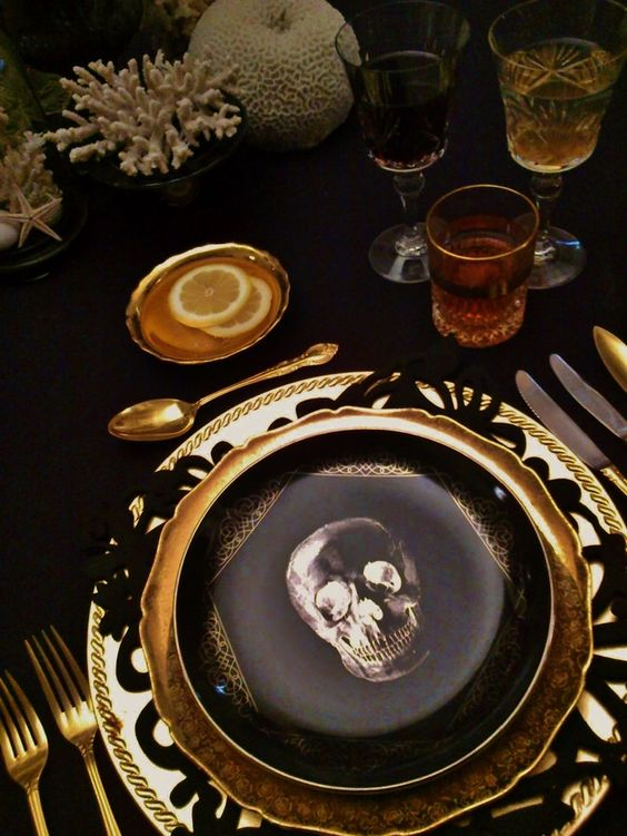 a stylish place setting with a skull print plate, a gold charger and cutlery
