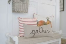 13 a vintage bench with pillows, a basket with dried flower over it