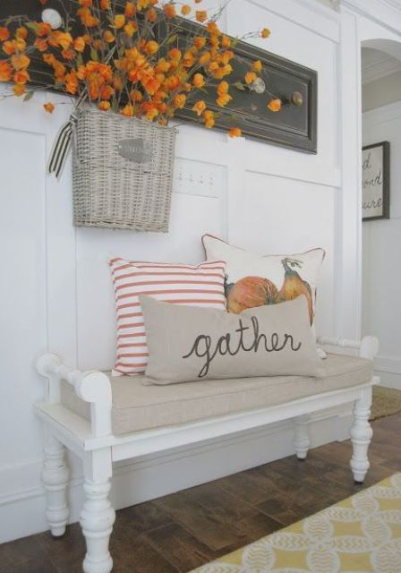 a vintage bench with pillows, a basket with dried flower over it