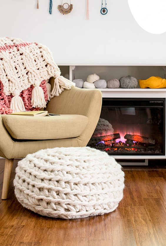 a white chunky knit ottoman or footrest is a cozy piece to sit on next to the fireplace