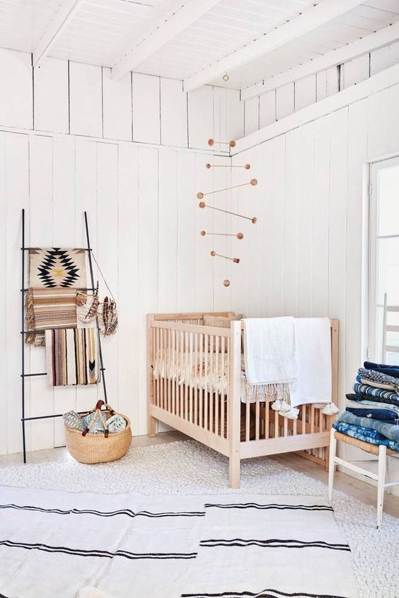 a wooden crib, a wicker basket and a wooden mobile add a cozy rustic feel to the space