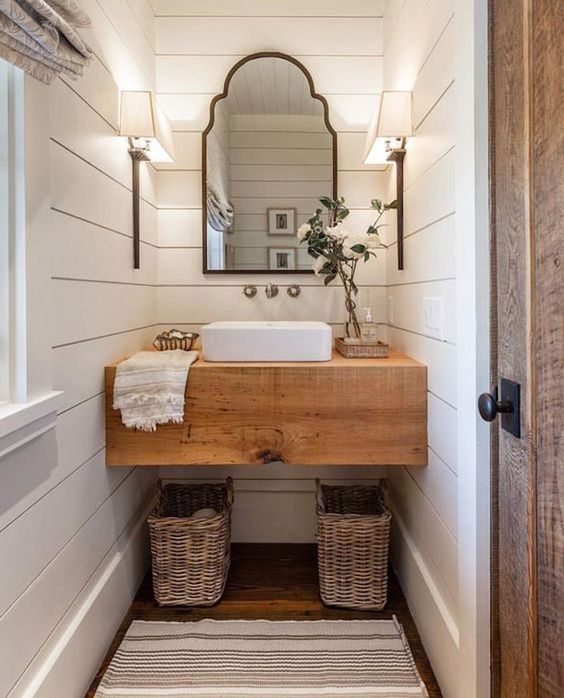 a wooden vanity and baskets under the vanity for a cozy rustic space