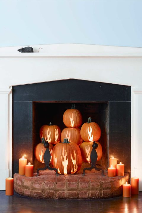If you're always thinking you don't use your fireplace enough, this fun decoration was made for you. Carve flames into pumpkins for a cozy atmosphere
