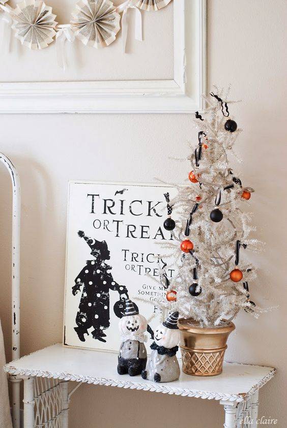 a Halloween tree with orange and black ornaments, a black and white sign and some figurines