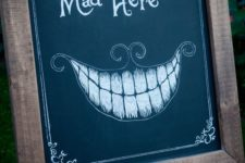 14 a chalkboard sign with an Alice In Wonderland inspired image and phrase