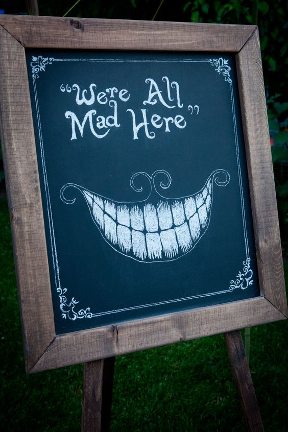 a chalkboard sign with an Alice In Wonderland inspired image and phrase