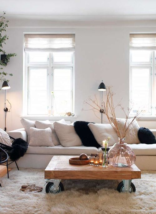 a neutral faux fur rug and black faux fur pillows to cozy up the living room