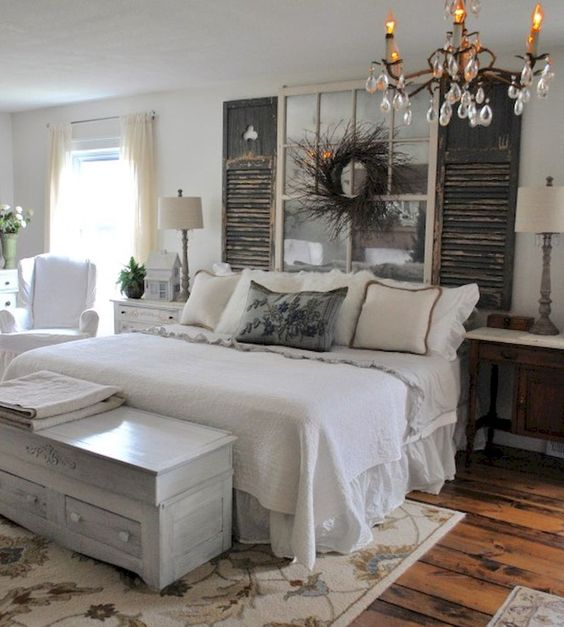 a rustic farmhouse bedroom with a vintage door headboard, whitewashed furniture and wood floors