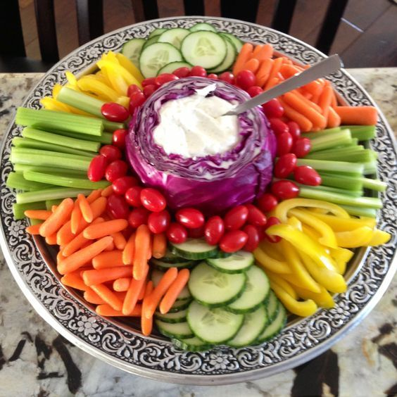 a veggie tray with dip placed into a cabbage for a cute and cozy rustic look