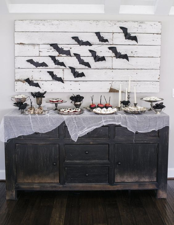 a vintage sideboard covered with cheesecloth and a pallet sign with bats for simple Halloween decor