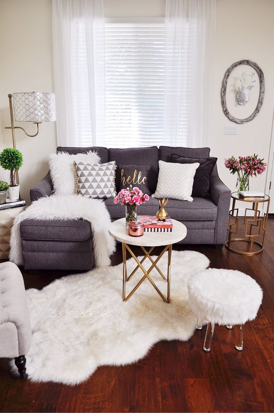a chic faux fur rug and a matching blanket and pillow turn this space into a glam winter one