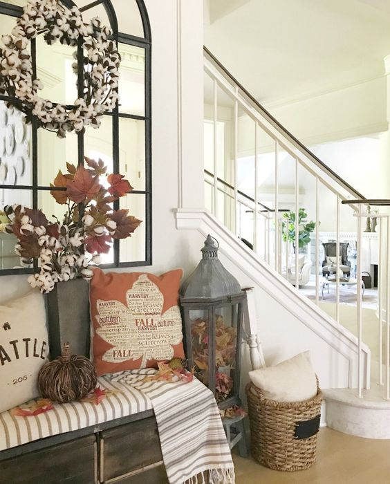 a wooden bench with fall leaves, fall pillows, cotton branches and a cotton wreath over the bench