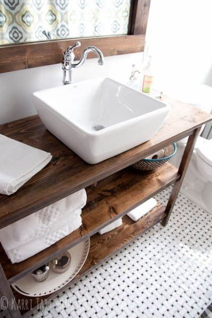 a wooden vanity with several shelves, a wood framed mirror for a cozy rustic space