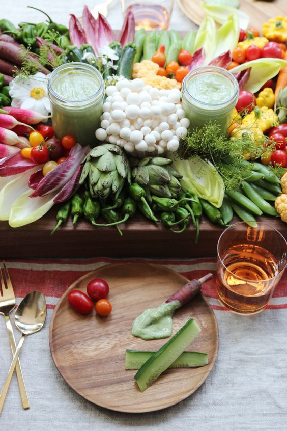 a wooden veggie tray with beautifully styled vegetables and dips