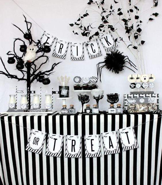 black and white dessert table with a faux tree and an owl, a spider and a banner