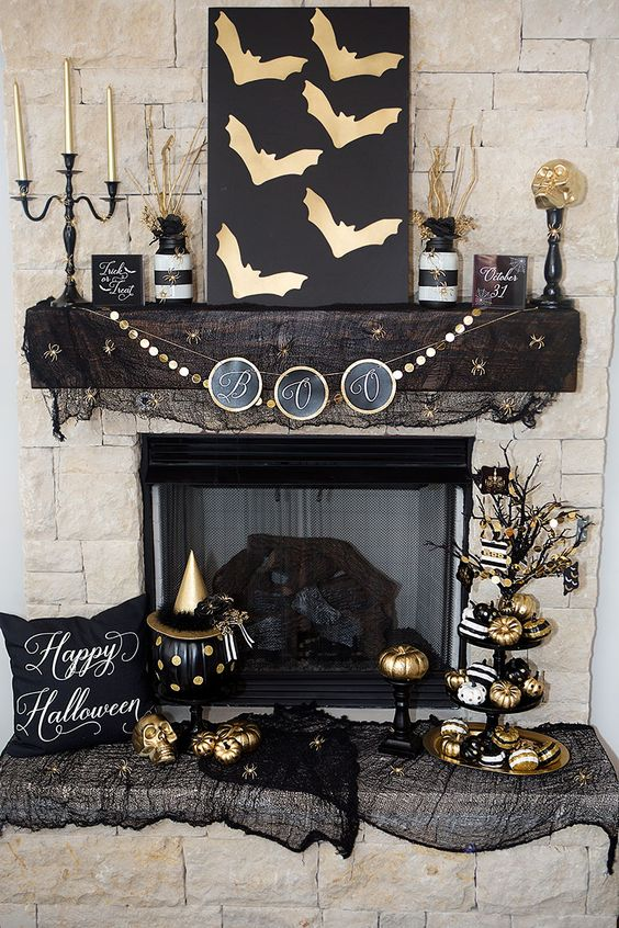stylish black and gold fireplace and mantel decor with a bat sign, candles, banners, pumpkins and lots more