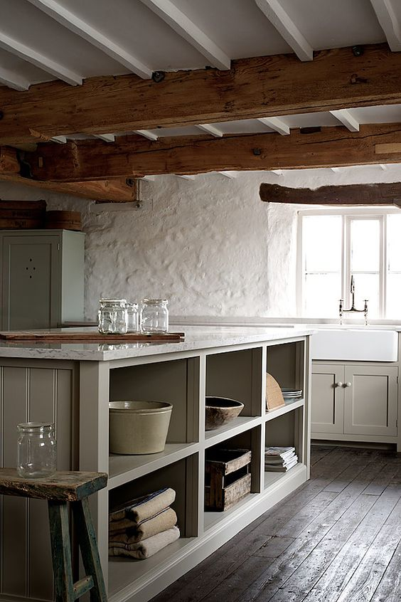 this rustic kitchen looks amazing with stucco walls and wooden beams