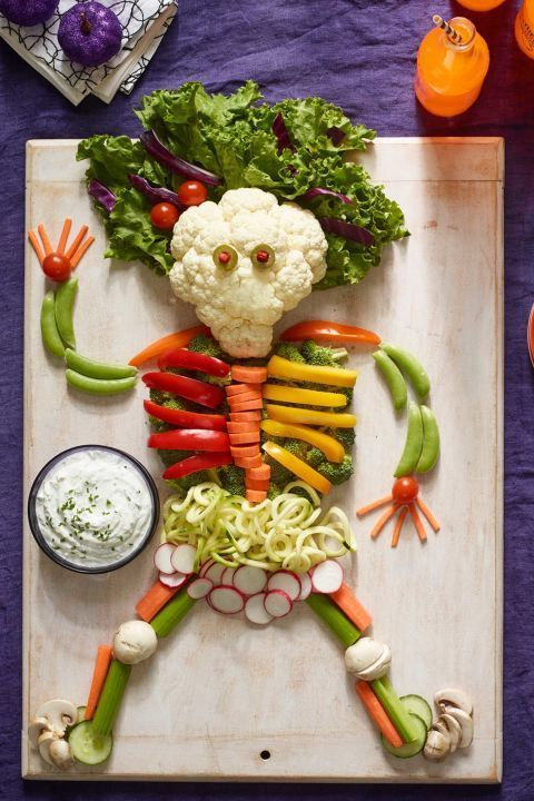 a veggie tray styled as a spooky human or skeleton and some dip next to it