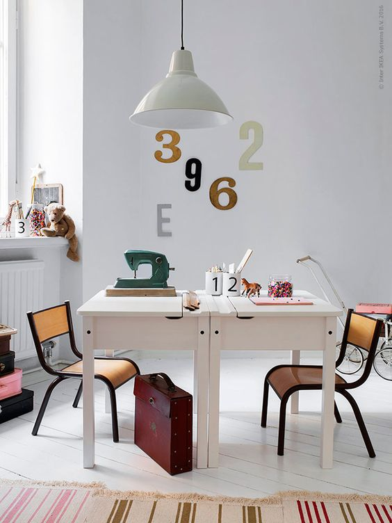 a cool study space with two desks facing each other, vintage chairs and numbers on the wall