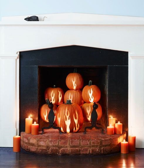 a fireplace with antler carved pumpkins and black cants and candles around