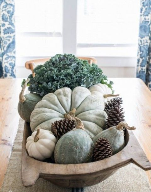 a large bowl with pale green pumpkins and gourds, greenery and pinecones for a rustic look