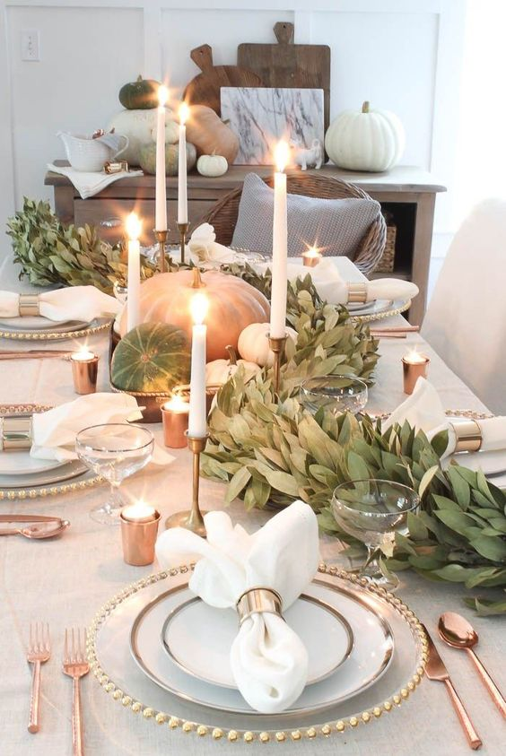 a modern tablescape with large pumpkins, a lush greenery table runner, candles and copper touches