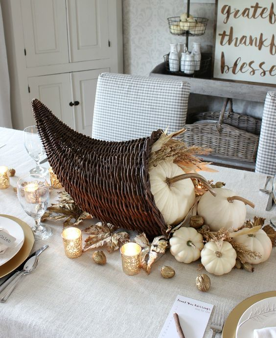 a rustic centerpiece of a cornucopia filled with white pumpkins, wheat and gilded faux leaves