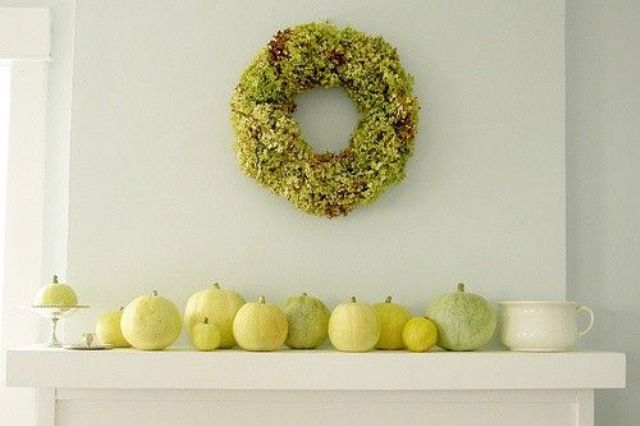 a selection of yellow and green pumpkins and a greenery wreath for a modern fall look