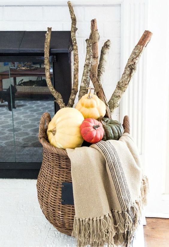 a tall basket with various pumpkins, large branches and a blanket by the fireplace