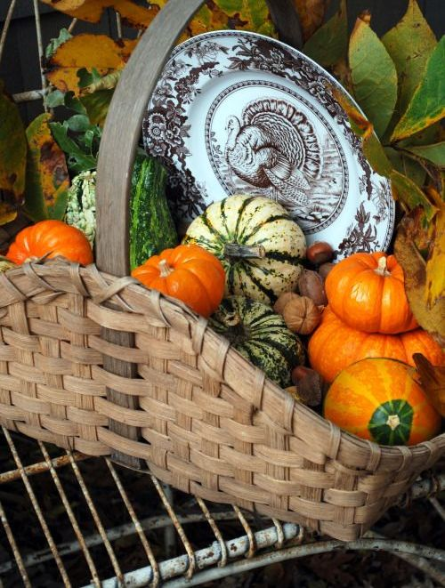 a basket with faux pumpkinsm gourds, fall leaves and a vintage place with a turkey