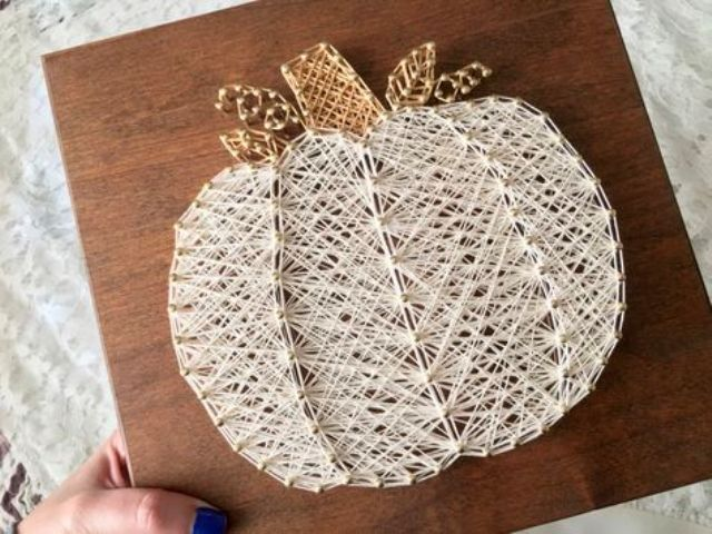 a chic creamy pumpkin string art with a gold stem for Thanksgiving