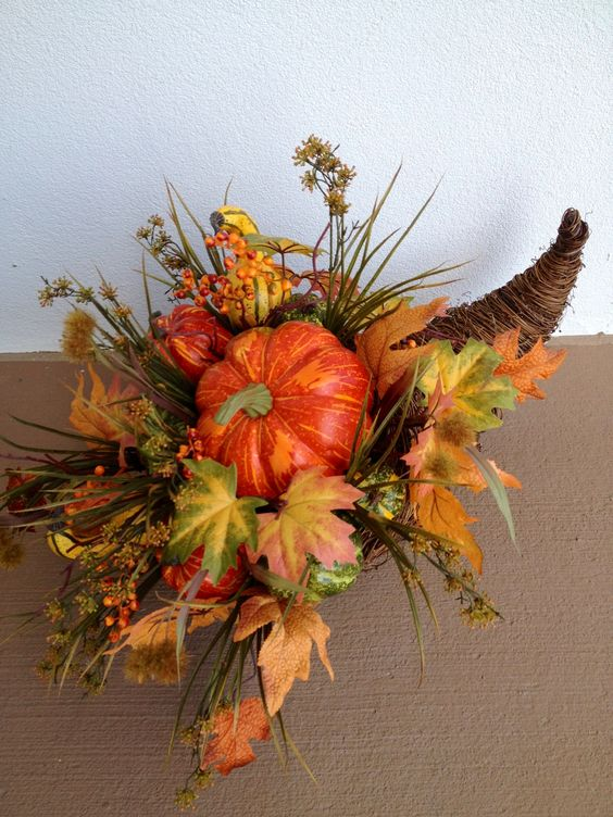 a fall cornucopia with faux leaves, grass and pumpkins in bold fall colors